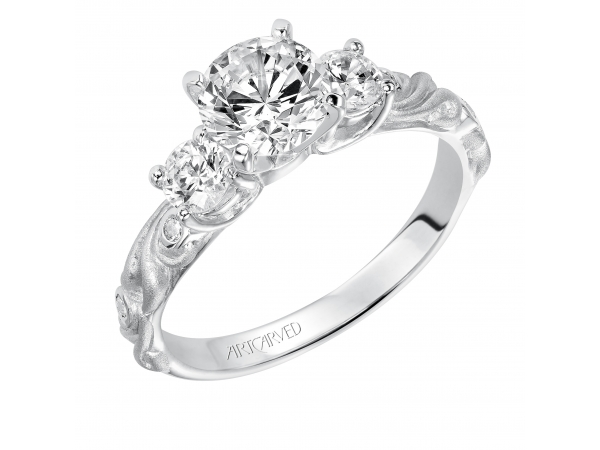 Fanciful - Diamond three stone engagement ring with round center, round side stones and a satin finished floral carving detail highlighted with diamonds.