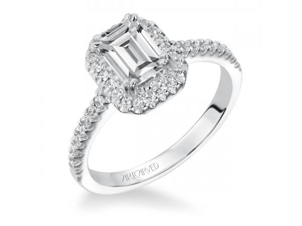 Annie - Diamond engagement ring with emerald cut center stone, round diamonds surrounding the center stone, and a diamond enhanced band.
